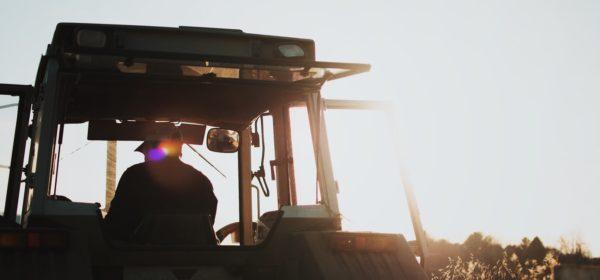 Un agriculteur sur son tracteur labourant son champ