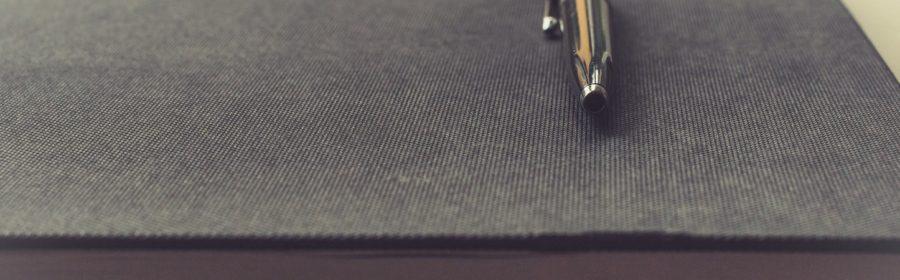 un stylo posé sur un cahier de note.