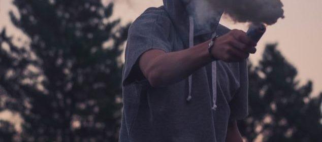 Un jeune homme avec un vêtement à capuchon, tenant un fumigène.