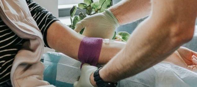 Un medecin attachant un garrot sur le bras gauche d'une patiente à son domicile.